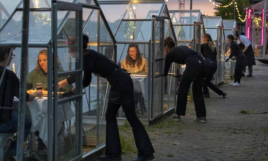 Voluntários são servidos em cabines de vidro no restaurante Mediamatic ETEN em Amsterdã. Restaurantes fizeram testes de como operar com distanciamento social para que pudessem reabrir depois da primeira onda da pandemia Foto: ILVY NJIOKIKTJIEN / Agência O Globo - 12/05/2020