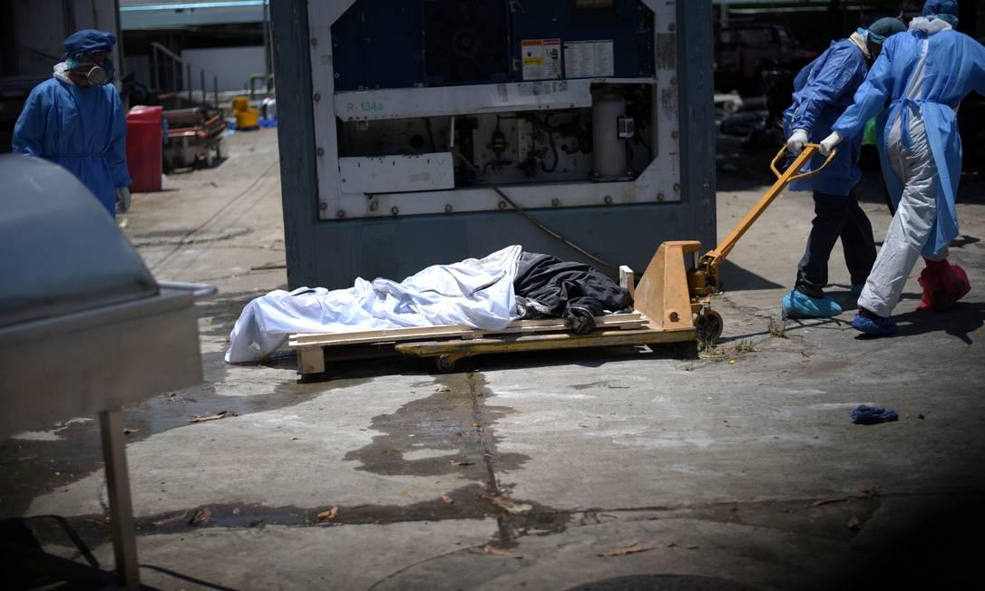 Profissionais de saúde vestindo equipamentos de proteção carregam cadáver no entorno do Hospital Teodoro Maldonado Carbo, em Guayaquil, Equador, onde contêineres foram instalados para conservar corpos de vítimas da Covid-19 Foto: Vicente Gaibor del Pino / Reuters - 03/04/2020
