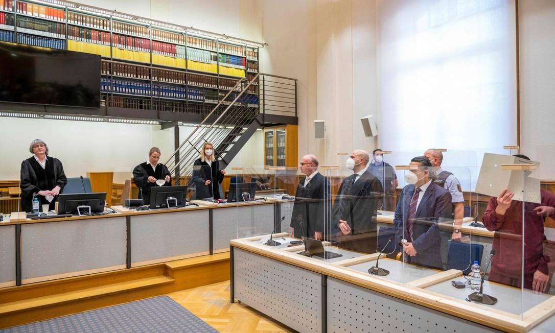 Juíza Anne Kerber, à esquerda, se apresenta antes de dar o veredicto ao réu sírio Eyad al-Gharib, escondido sob uma pasta, acusado de crimes contra a humanidade no primeiro julgamento desse tipo a emergir do conflito na Síria, em Koblenz, oeste da Alemanha. Foto: THOMAS LOHNES / AFP
