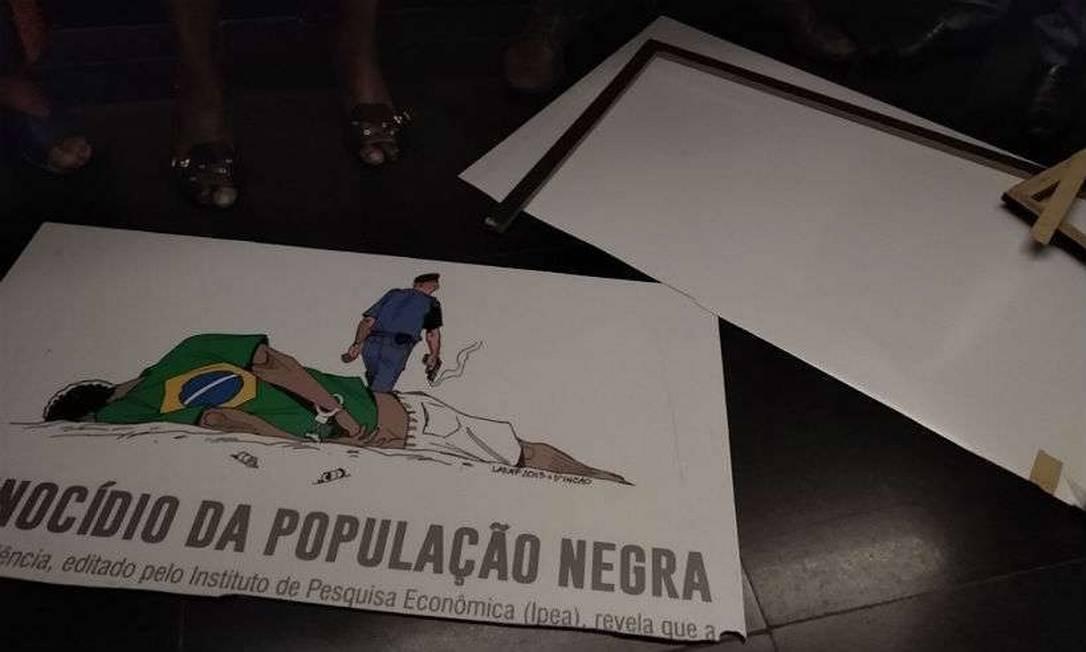 Placa quebrada em uma exposição da Câmara exibia um desenho que associava a polícia a genocídio de negros Foto: Reprodução
