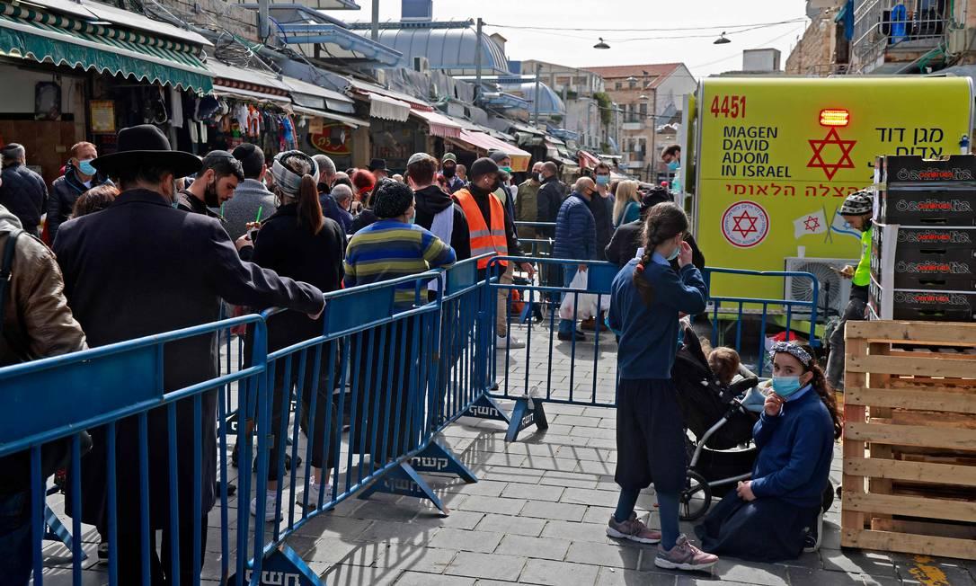 Pessoas fazem fila para receber doses da vacina contra a Covid-19 em Jerusalém Foto: MENAHEM KAHANA / AFP