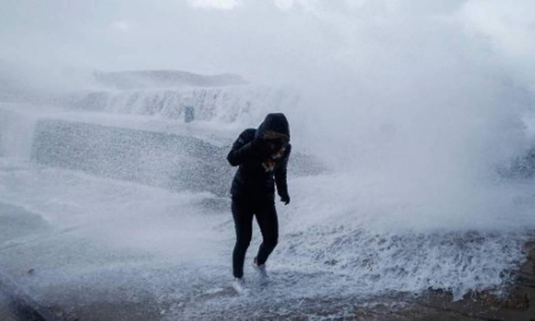 Mulher se protege de ondas em Auderville, na França, em 2018: a Tempestade Eleanor provocou ventos de até 155 km/h e forçou o fechamento da Torre Eiffel Foto: CHARLY TRIBALLEAU/AFP