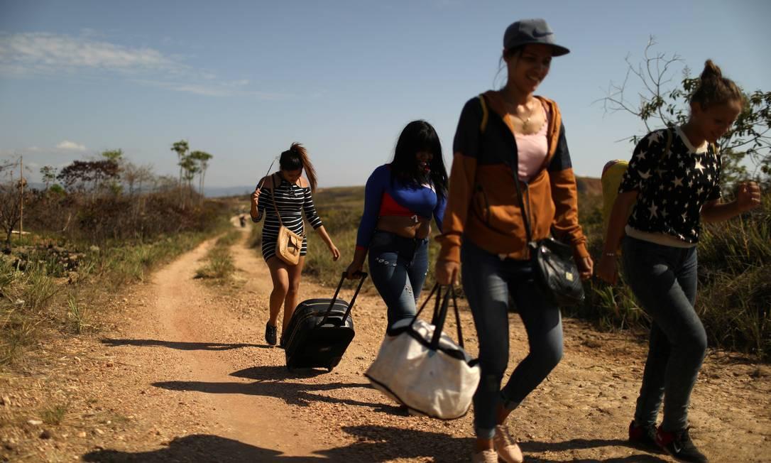 Migrantes venezuelanos caminham por uma trilha na cidade fronteiriça de Pacaraima Foto: Pilar Olivares / Agência O Globo