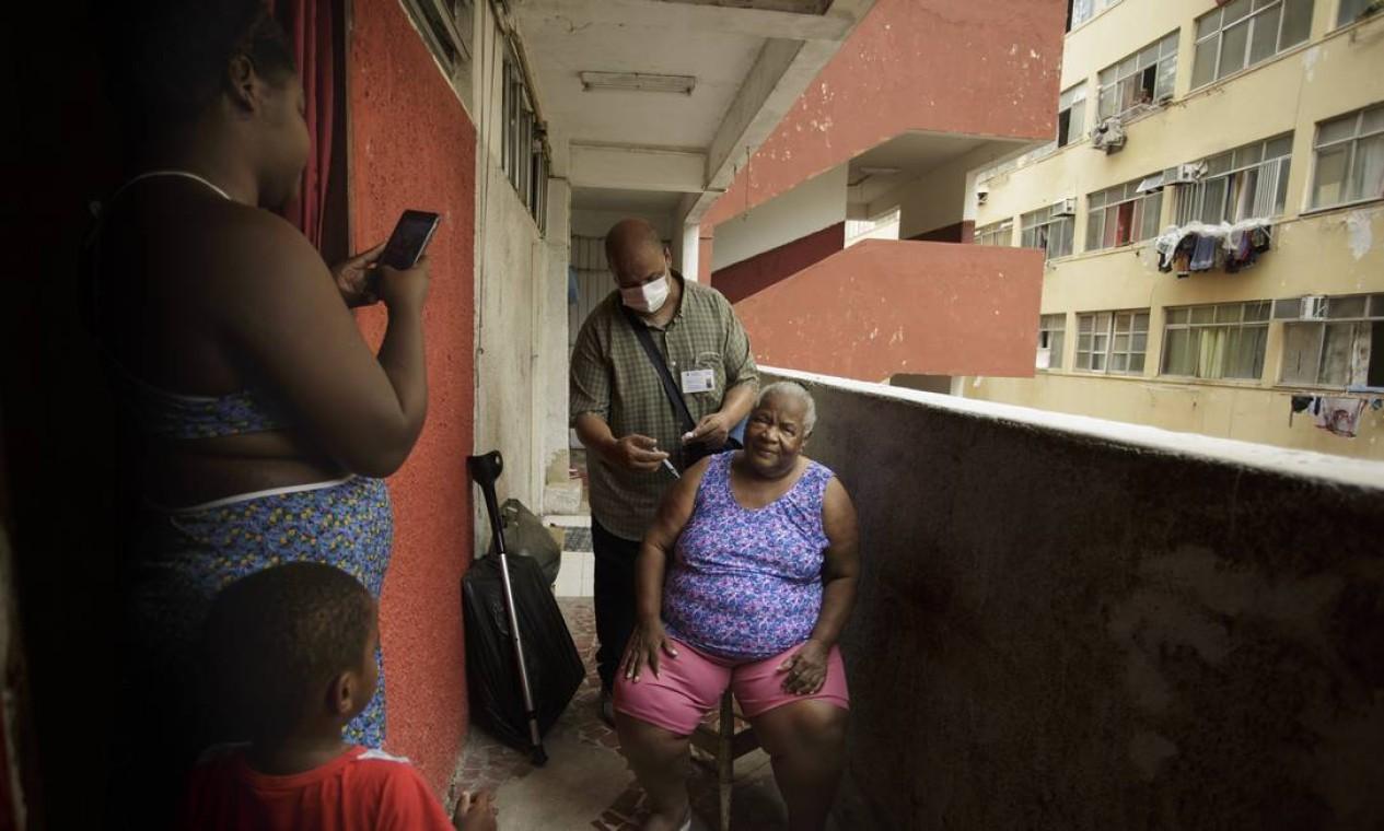 Dijanira Chagas da Silva, de 86 anos, é imunizada contra a Covid-19 em sua casa, na Cruzada São Sebastião, no Leblon. Equipe Trombeta, da Secretaria Municipal de Saúde, faz a vacinação em casa de idosos com dificuldades de locomoção Foto: Márcia Foletto / Agência O Globo