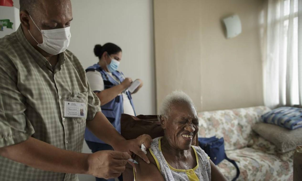 O técnico de enfermagem Milton Gomes Nunes Júnior aplica a vacina em Maria Palmira Maximiliano, de 87 anos, enquanto a agente comunitária Íris da Silva Brito preenche as carteirinhas de vacinação Foto: Márcia Foletto / Agência O Globo