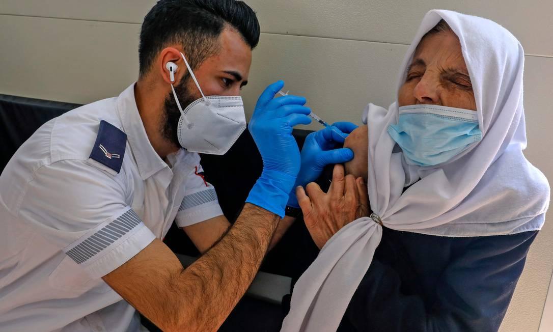 Paramédico aplica vacina em mulher palestina na Cidade Velha de Jerusalém Foto: AHMAD GHARABLI / AFP
