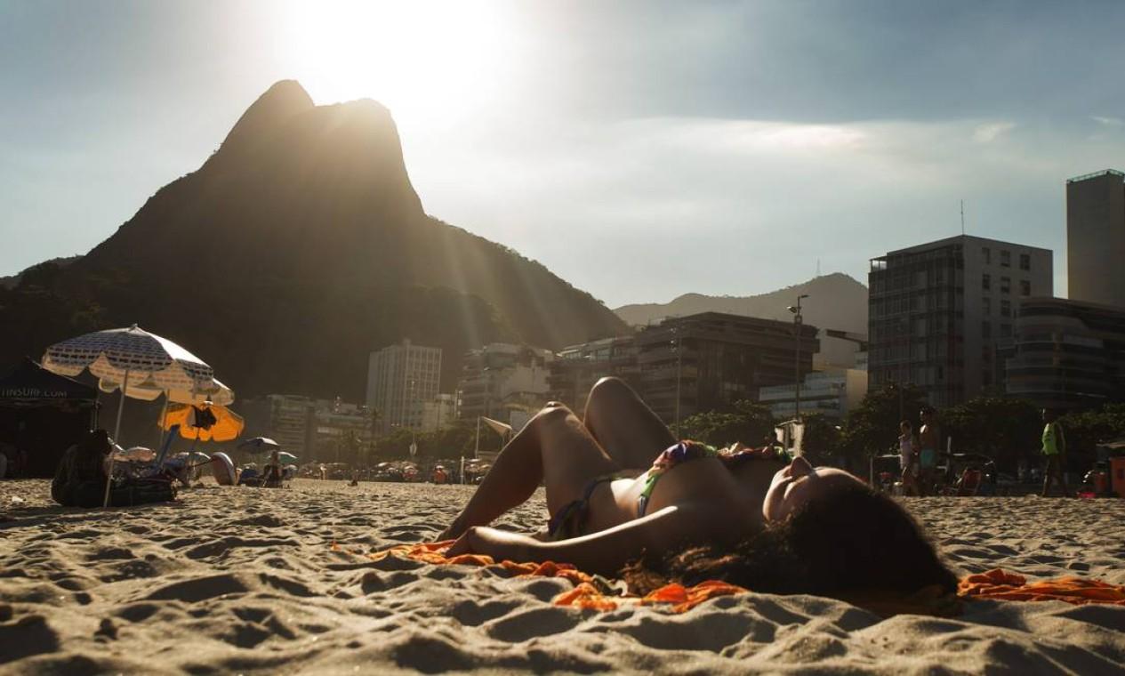 Banhista na praia do Leblon, com o Morro Dois Irmãos ao fundo Foto: Antônio Scorza / Agência O Globo