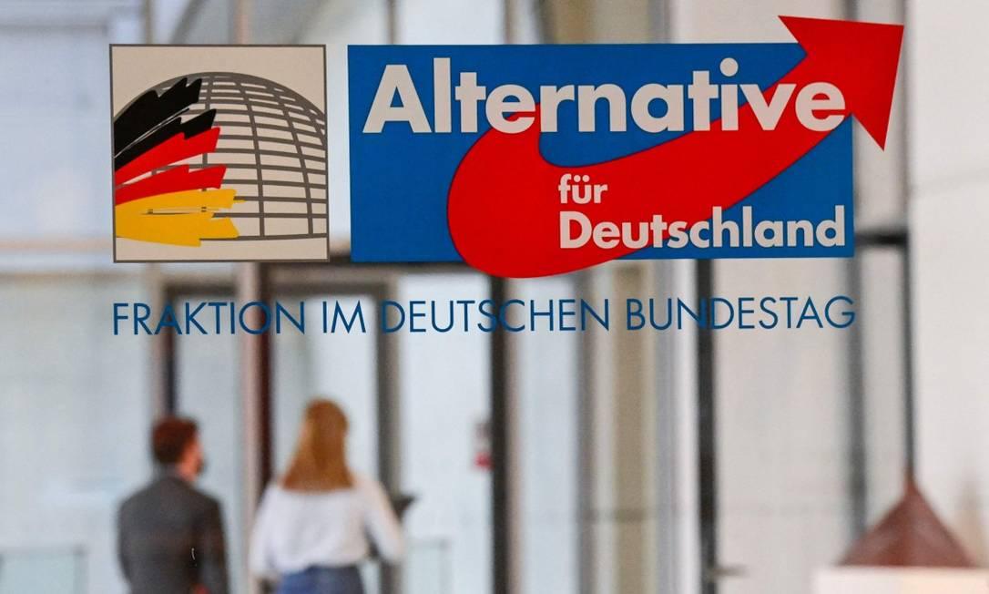 Pessoas caminham atrás de parede de vidro com logo da Alternativa para a Alemanha no Budenstag, o Parlamento do país Foto: TOBIAS SCHWARZ / AFP