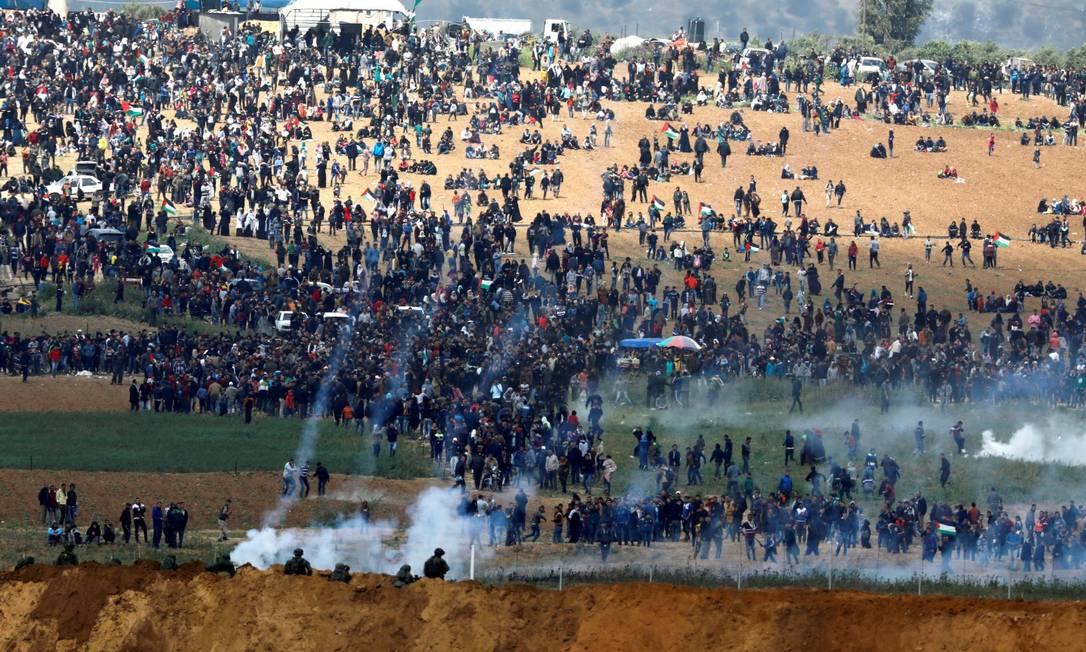 Soldados israelenses disparam gás lacrimogêneo do lado israelense da fronteira entre Israel e Gaza, enquanto palestinos protestam no lado da fronteira em Gaza. Foto: AMIR COHEN/ 30/03/2018 / REUTERS