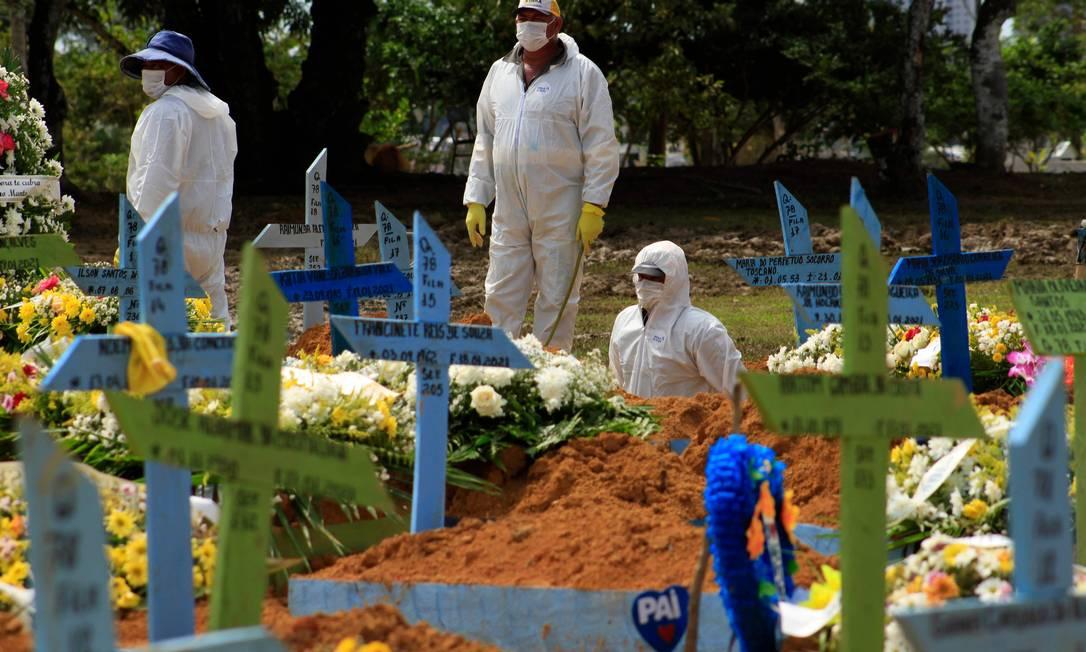 Coveiros durante o funeral de uma vítima de Covid-19 no cemitério Nossa Senhora Aparecida em Manaus, estado do Amazonas, Brasil, em 22 de janeiro de 2021 Foto: MARCIO JAMES / AFP