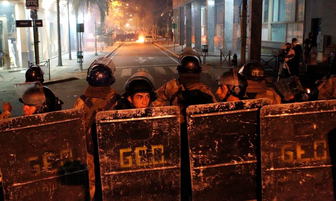 Policiais de choque em formação durante os confrontos em Assunção, Paraguai, enquanto manifestantes protestam contra as políticas de saúde do presidente Mario Abdo Benitez e a falta de vacinas contra o coronavírus Foto: CESAR OLMEDO / REUTERS/05-03-2021