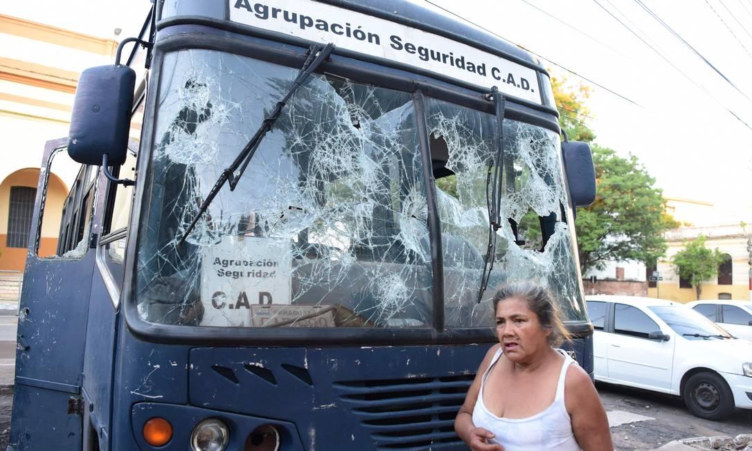 Mulher passa por ônibus cujas janelas foram quebradas durante um protesto contra má gestão do presidente Benítez contra a pandemia da Covid-19 Foto: NORBERTO DUARTE / AFP
