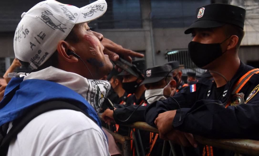 Manifestante enfrenta policial durante protesto contra má gestão na pandemia do presidente paraguaio, Mario Abdo Benítez Foto: NORBERTO DUARTE / AFP