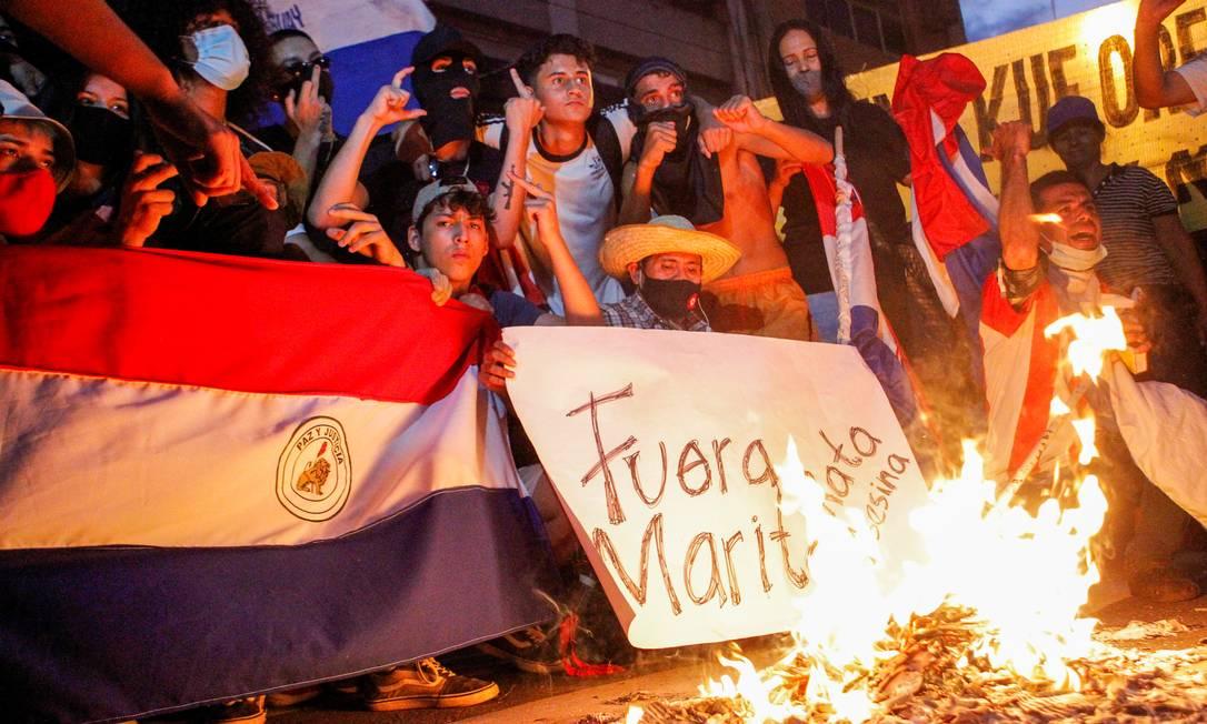 Manifestantes se reúnem em volta de fogueira para pedir a saída do presidente Mario Abdo Benítez Foto: CESAR OLMEDO / REUTERS