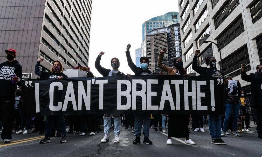 """Manifestantes seguram uma faixa com os dizeres """"Eu Não Consigo Respirar"""" em frente ao Centro Governamental do Condado de Hennepin, onde o julgamento do ex-policial de Minneapolis, Derek Chauvin, acusado de assassinar o afro-americano George Floyd, acontecerá. Foto: CHANDAN KHANNA / AFP"""