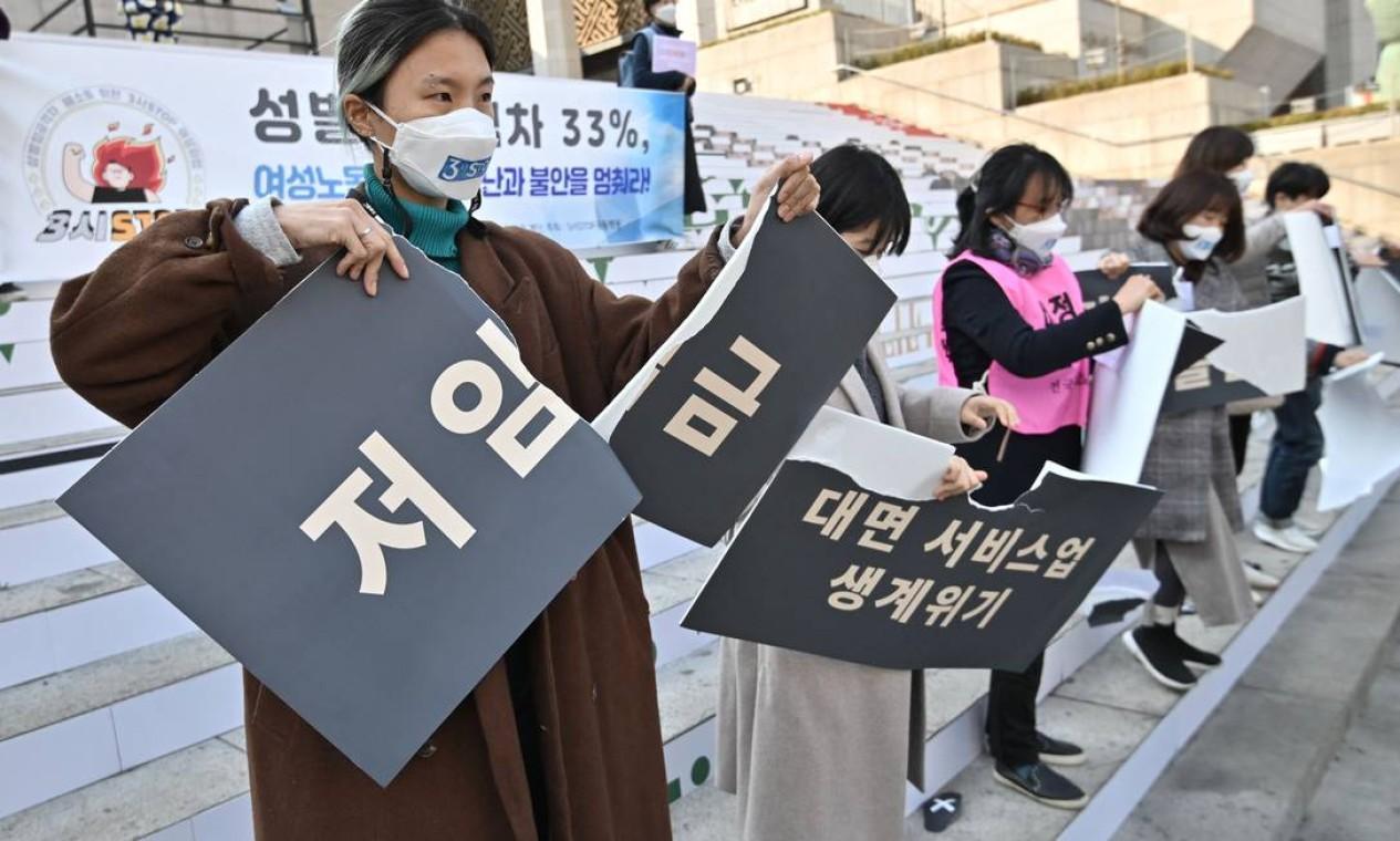 Ativistas sul-coreanas rasgam cartazes sobre discriminação contra mulheres durante um protesto para marcar o Dia Internacional da Mulher em Seul Foto: JUNG YEON-JE / AFP