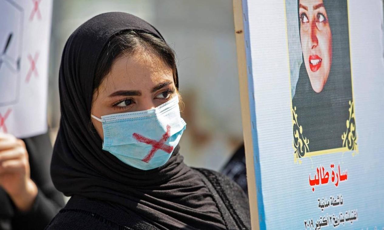 Mulher iraquiana protesta contra o silenciamento, usando máscara riscada, na cidade de Basra, no sul do Iraque Foto: HUSSEIN FALEH / AFP