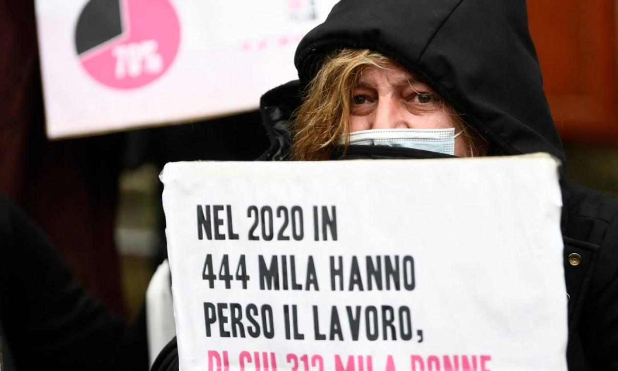 """Uma mulher segura um cartaz que diz em italiano """"em 2020, 312.000 dos 444.000 trabalhadores que perderam seus empregos eram mulheres"""", durante uma manifestação convocada pelo movimento Non una di Meno (Nem uma a menos) contra o entrecruzamento do patriarcado, neoliberalismo e racismo, em frente ao Ministério da Economia italiano por ocasião do Dia Internacional da Mulher Foto: FILIPPO MONTEFORTE / AFP"""