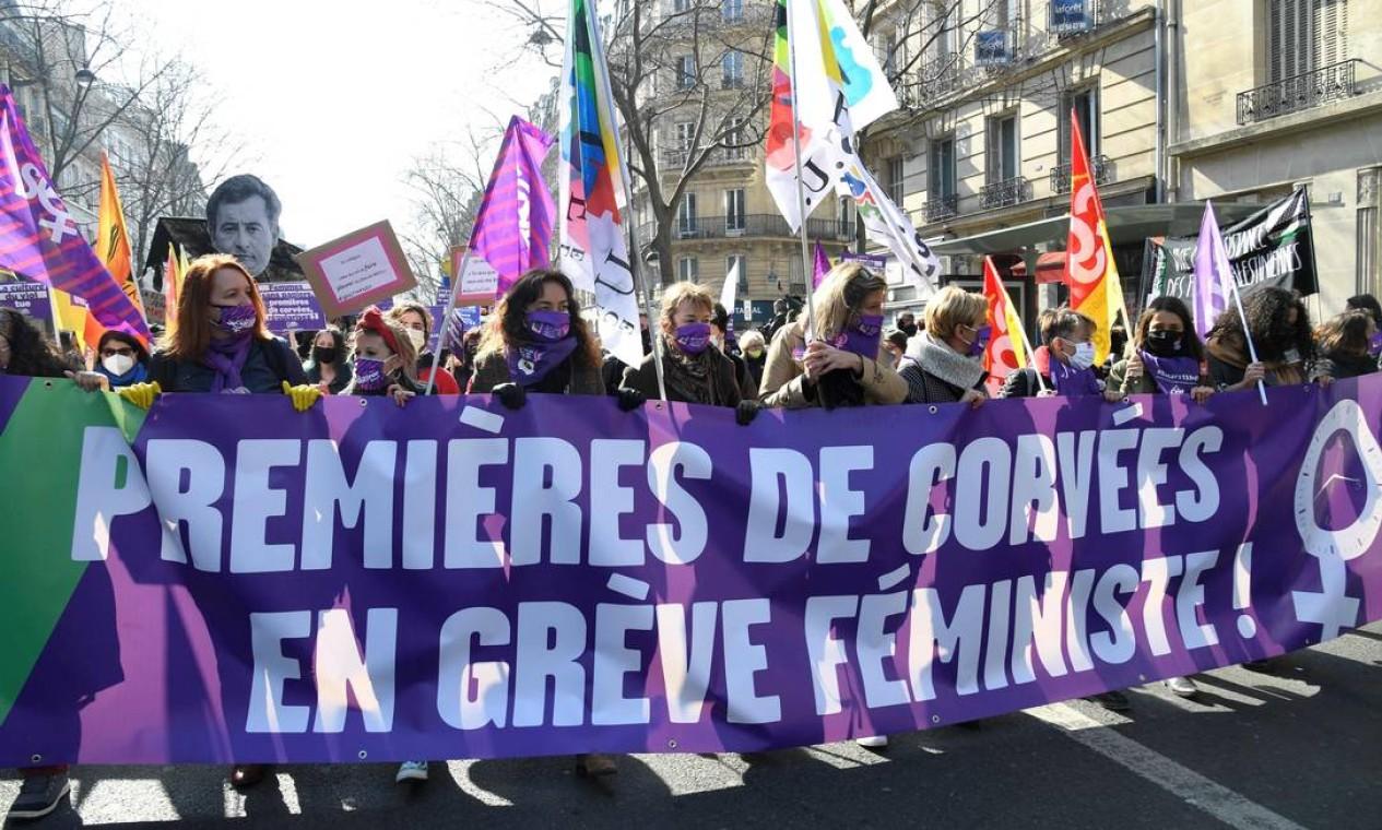 """Mulheres seguram uma faixa com os dizeres """"Primeiras a trabalhar. Feministas em greve"""", em protesto por mais direitos para as mulheres como parte do Dia Internacional da Mulher, em Paris, França Foto: BERTRAND GUAY / AFP"""