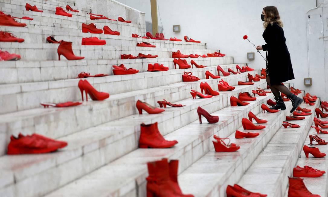 Mulher coloca uma flor vermelha em uma instala??o de sapatos vermelhos femininos exibidos na escada, como um símbolo para denunciar a violência contra as mulheres, na pra?a principal de Durresi, em Tirana, Albania Foto: GENT SHKULLAKU / AFP