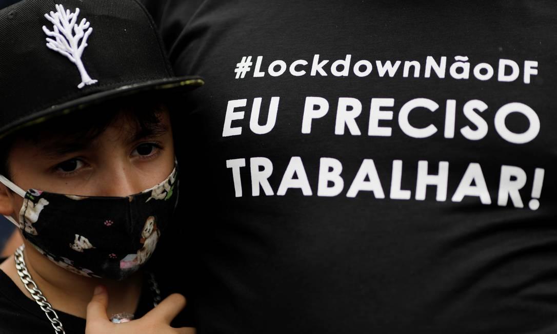 Criança usando máscara abraça adulto que veste camisa de protesto contra o lockdown em Brasília, apesar dos números da pandemia Foto: UESLEI MARCELINO / REUTERS - 28/02/2021