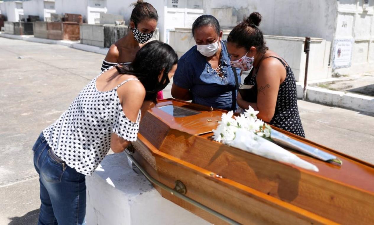 Parentes de Luiz Alves, 63, vítima da COVID-19, reúnem-se ao redor do caixão no cemitério de Inhaúma, no Rio de Janeiro Foto: Pilar Olivares / Reuters - 10/03/2021