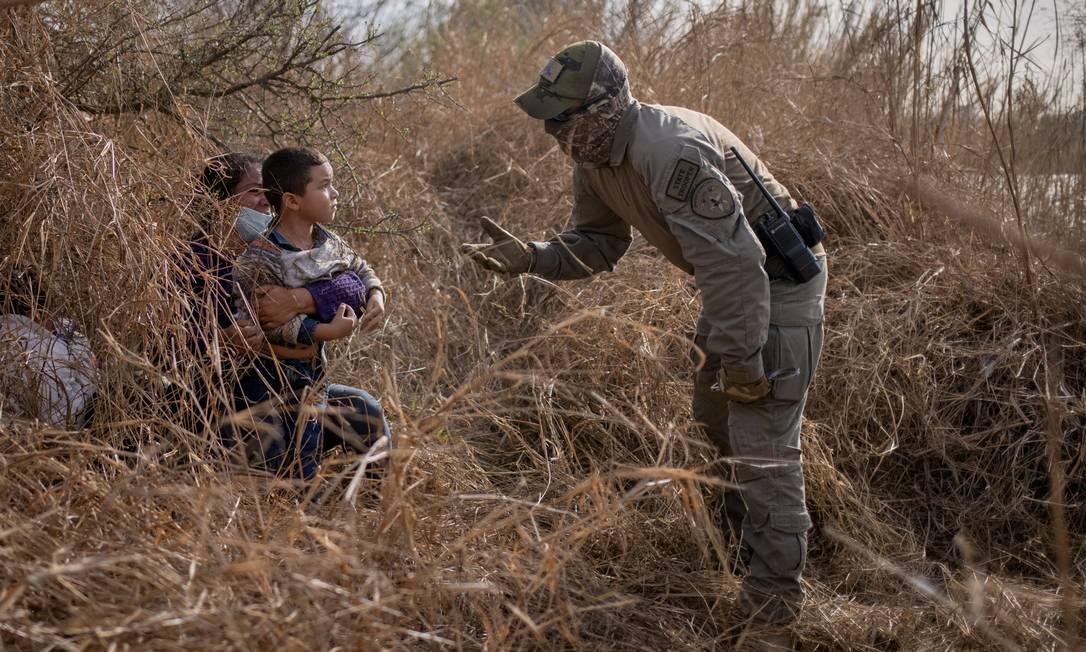 Um policial estadual do Texas conversa com Edith e seu filho Harbin Ordonez, de 4 anos, perto do Rio Grande Foto: ADREES LATIF / REUTERS