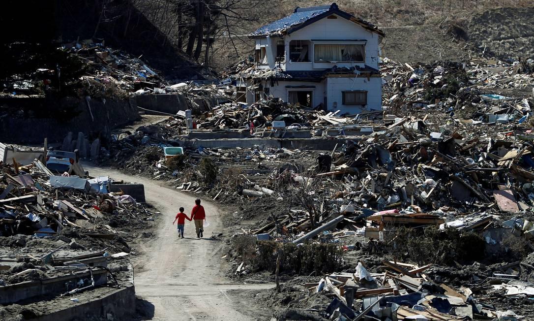 Pessoas caminham por destroços do tsunami e do terremoto em Miyako, no dia 5 de abril de 2011 Foto: Toru Hanai / REUTERS