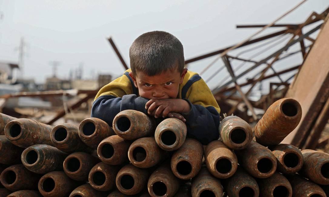 Crian?a síria posa sobre uma pilha de projéteis neutralizados em um ferro-velho de metal nos arredores da cidade de Maaret Misrin, na província de Idlib, no noroeste do país Foto: AAREF WATAD / AFP - 10/03/2021