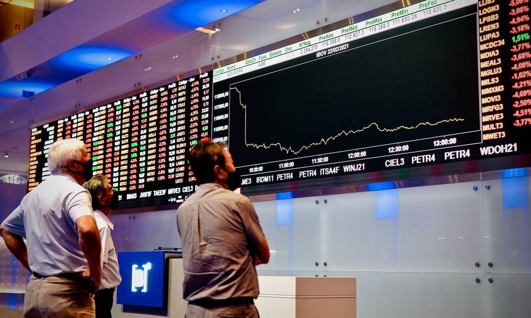 Movimentação em torno do painel da B3 que mostra forte queda na bolsa de valores em São Paulo, em razão da troca de comando na Petrobras e falas do presidente Bolsonaro Foto: Marco Ankosqui / Agência O Globo
