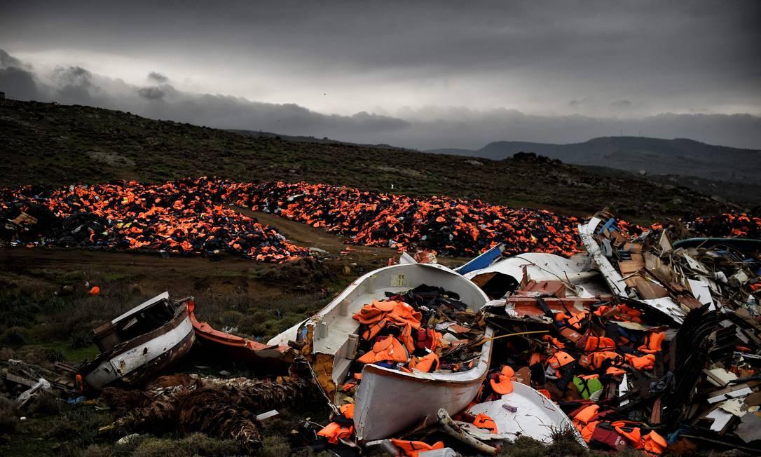 Destroços de barcos naufragados e milhares de coletes salva-vidas usados por refugiados e migrantes durante sua jornada pelo mar Egeu estão em um lixão em Mithimna, Grécia Foto: ARIS MESSINIS / AFP