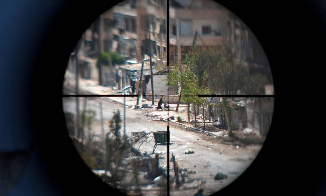 Mulher e seu bebê são vistos através da mira de um atirador de elite, enquanto foge do bairro de Saif al-Dawla, na cidade de Aleppo, no norte da Síria Foto: ZAC BAILLIE / AFP/29-8-2012