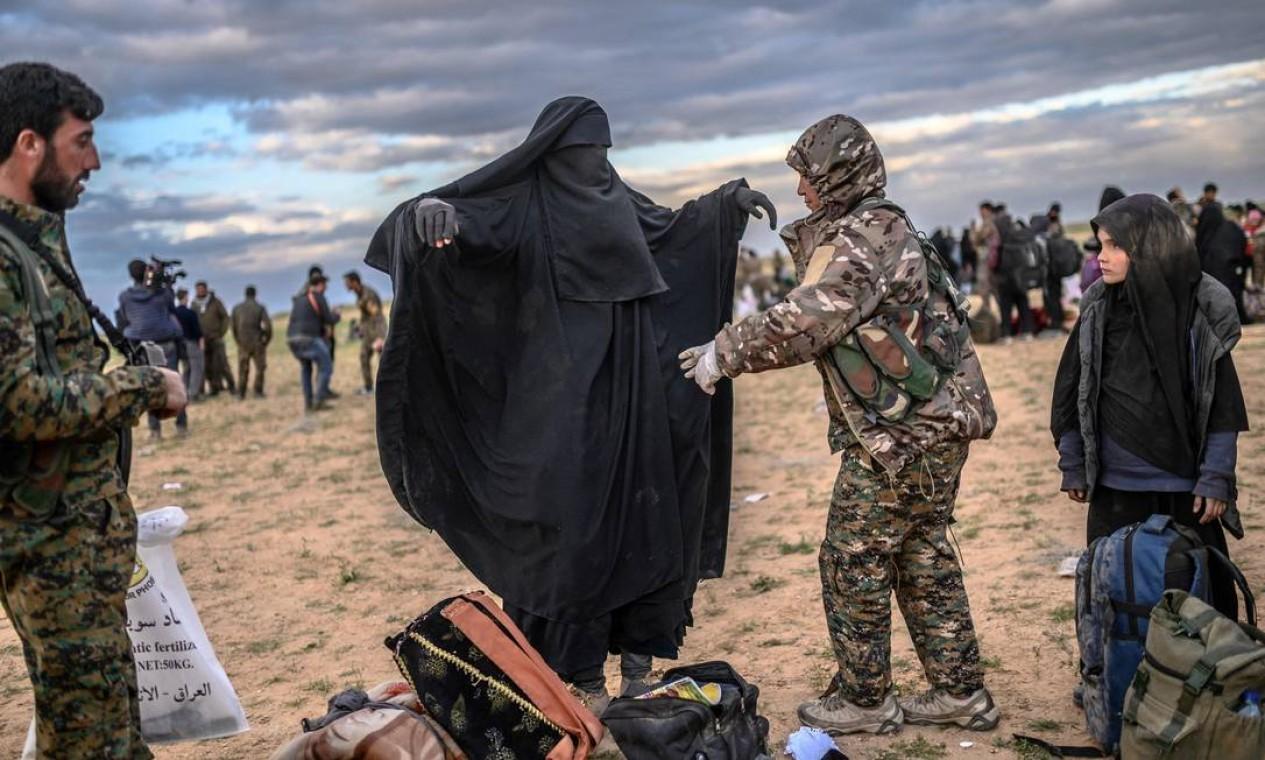 Membro das Forças Democráticas Sírias lideradas por curdos (SDF) revista uma mulher depois que ela deixou o último reduto do grupo IS em Baghouz, na província de Deir Ezzor, no norte da Síria Foto: BULENT KILIC / AFP - 27/02/2019