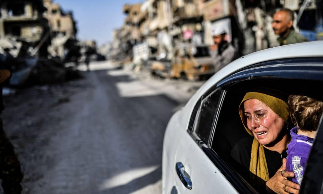 Mulher chora ao olhar para sua casa em Raqa, depois que uma força liderada por curdos expulsou o grupo do Estado Islâmico da cidade do norte da Síria Foto: BULENT KILIC / AFP - 20/10/2017