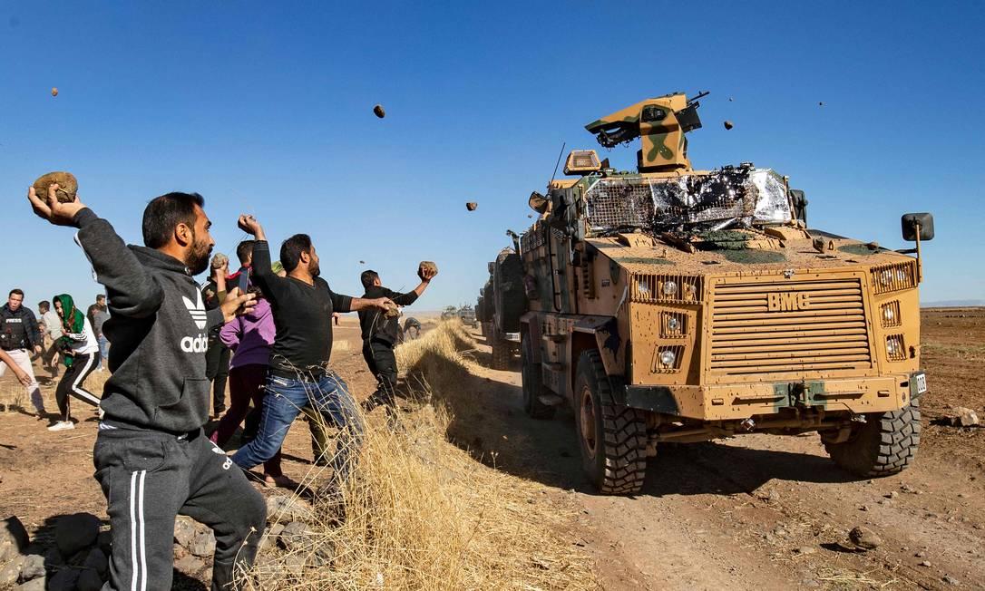 Curdos jogam pedras em um veículo militar turco, durante uma patrulha conjunta turco-russa perto da cidade de Al-Muabbadah, na parte nordeste de Hassakah, na fronteira da Síria com a Turquia Foto: DELIL SOULEIMAN / AFP - 08/11/2019