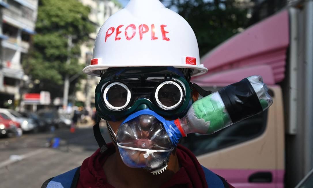 Com capacete de construção civil, óculos e garrafas PET, manifestante improvisa EPI Foto: STR / AFP
