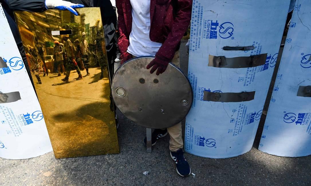Manifestantes exibem escudos improvisados usados em protestos em Yangon Foto: STR / AFP