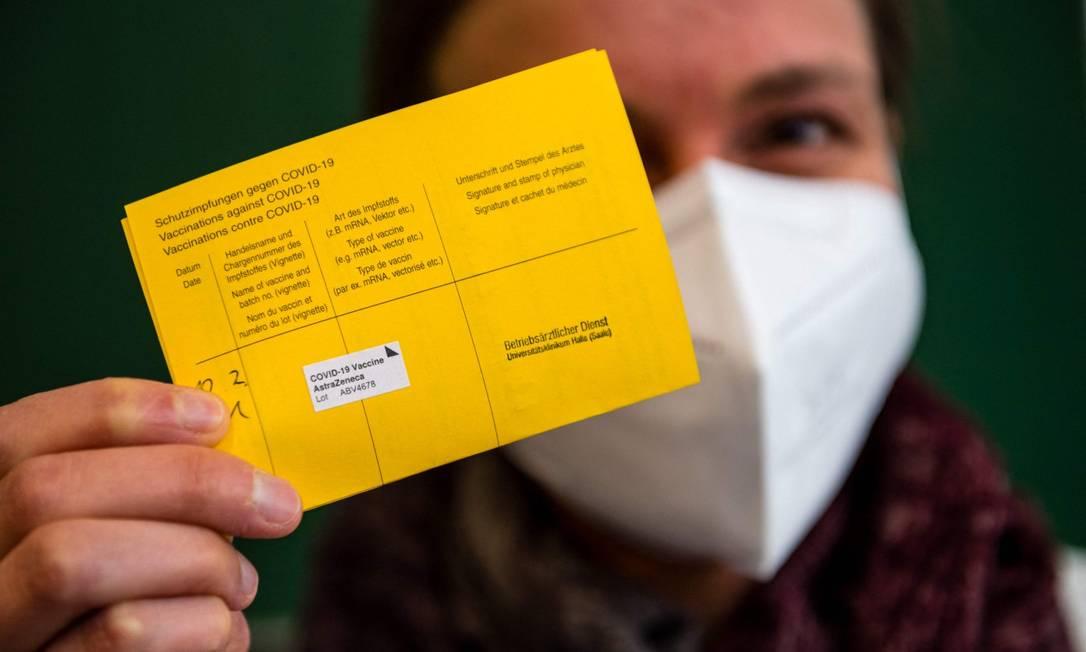 Mulher mostra seu certificado de vacinação após ser imunizada na cidade de Halle, no Leste da Alemanha Foto: JENS SCHLUETER / AFP / 12-2-21