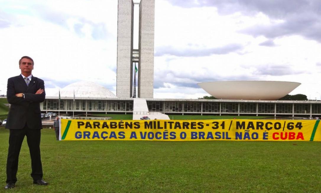 Bolsonaro, enquanto deputado, posa para foto com faixa em defesa do golpe militar de 64 Foto: Reprodução