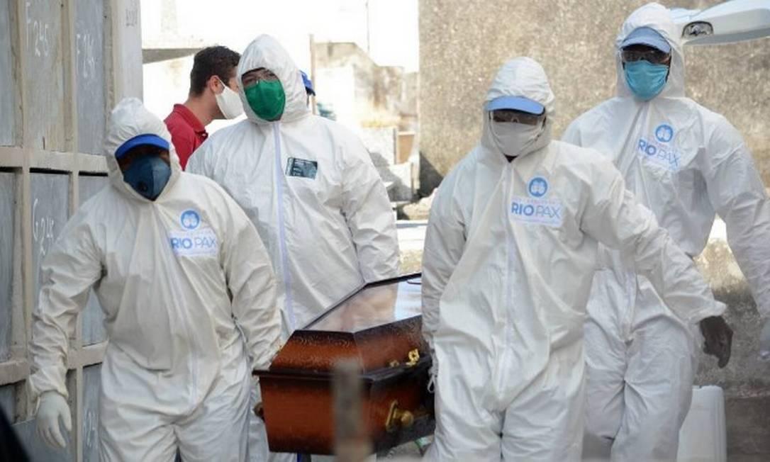 Vítima de Covid-19 é sepultada no cemitério de Irajá, na Zona Norte do Rio, por coveiros com equipamentos de proteção contra o novo coronavírus Foto: Jorge Hely / FramePhoto/Agência O Globo