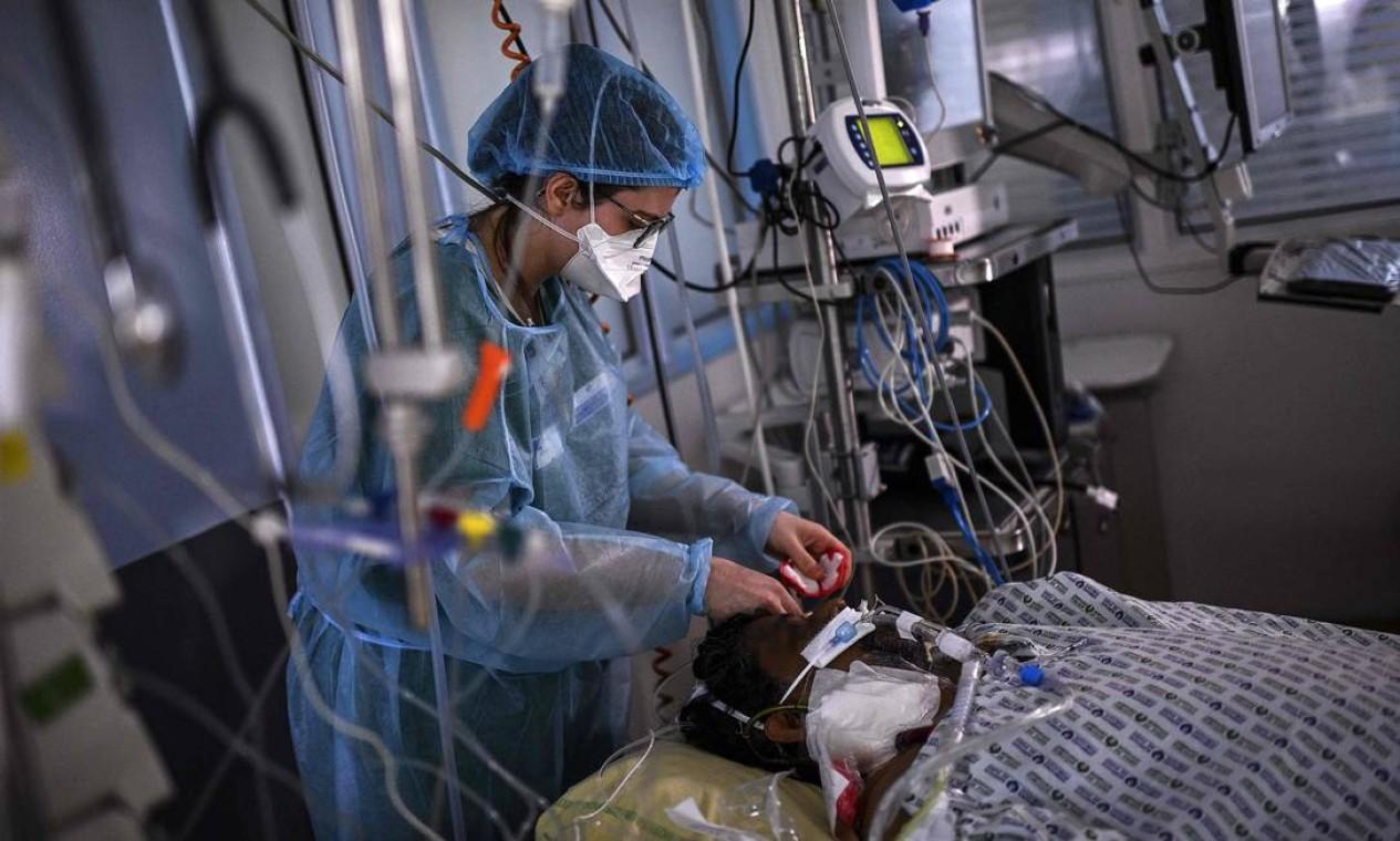 Enfermeira cuida de um paciente com Covid-19em um quarto da unidade de terapia intensiva do hospital AP-HP Cochin, em Paris. O novo coronavírus está novamente inundando os hospitais, onde equipes médicas preveem cenário sombrio Foto: CHRISTOPHE ARCHAMBAULT / AFP