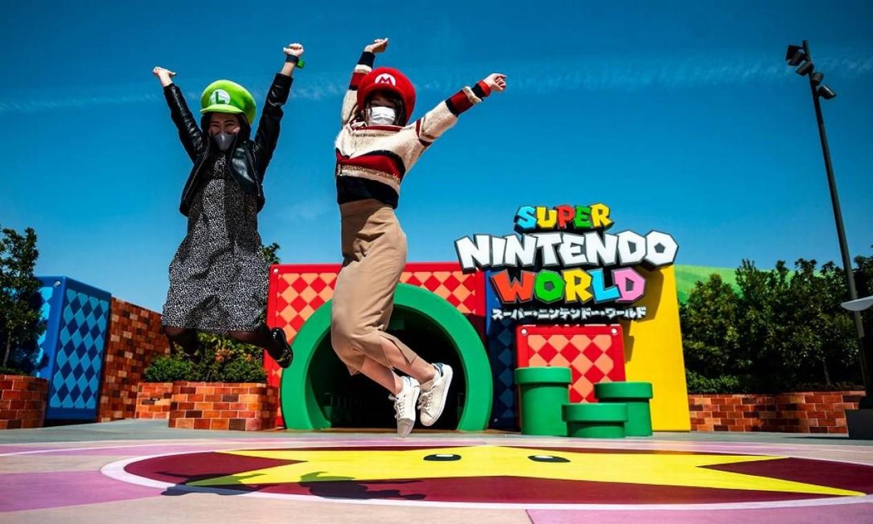 Duas visitantes com seus chapeus de Mario e Luigi saltam em frente ao túnel em forma de cano que dá acesso à área temática Super Nintendo World, do Universal Studio Japan Foto: Philip Fong / AFP