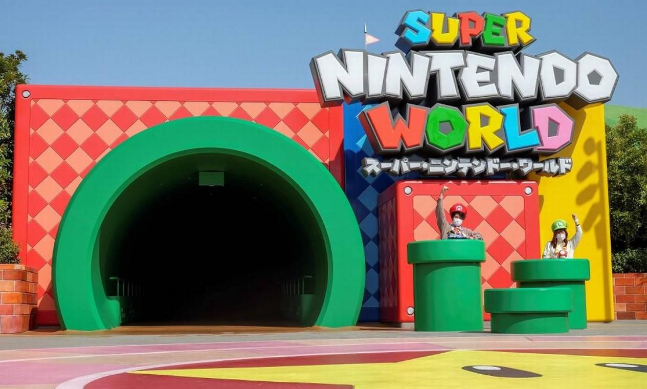 Duas visitantes com seus chapeus de Mario e Luigi posam em frente ao túnel em forma de cano que dá acesso à área temática Super Nintendo World, do Universal Studio Japan Foto: IRENE WANG / REUTERS