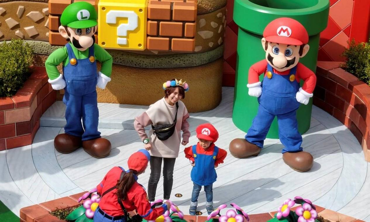 Mario e Luigi posam ao lado duas visiantes da Super Nintendo World, nova área temática do parque Universal Studios Japan, em Osaka Foto: IRENE WANG / REUTERS