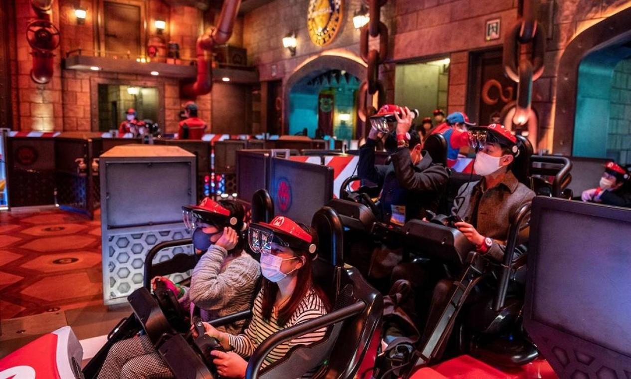 Visitantes a bordo de um dos carrinhos da atração baseada no jogo 'Mario Kart' na área Super Nintendo World, do parque Universal Studios Japan, em Osaka Foto: PHILIP FONG / AFP