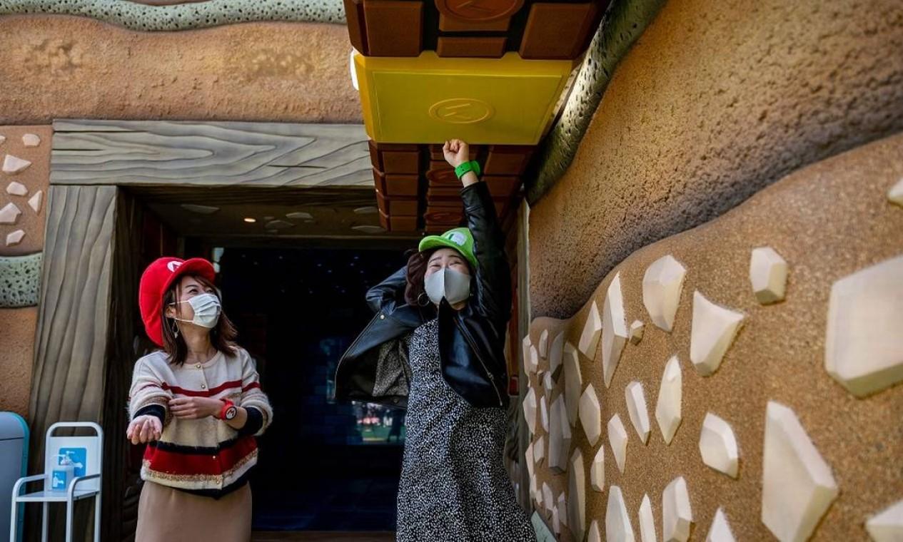 Visitante dá um soco num tijolo dourado na área interativa Koopa Troopa POWer Punch, do Super Nintendo World, no Universal Studios Japan, em Osaka. Será que caiu alguma moeda de ouro? Foto: PHILIP FONG / AFP