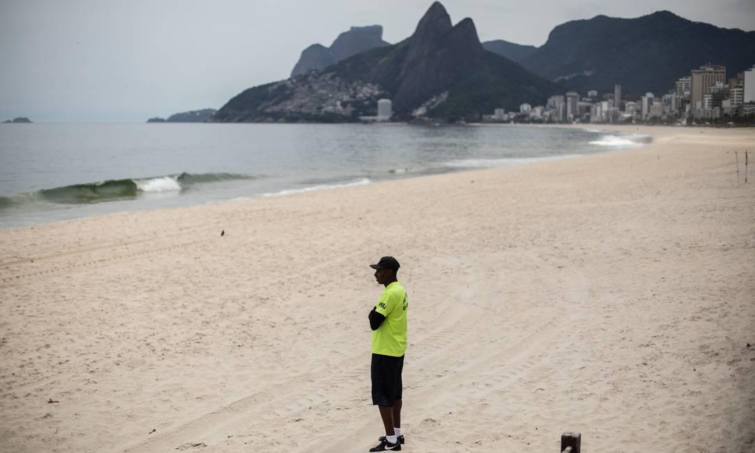 O uso das praias, como banho de mar, permanência nas areias e atividades físicas, está proibido no Rio. Na foto, um policial na praia Foto: Brenno Carvalho / O Globo - 31.03.2020