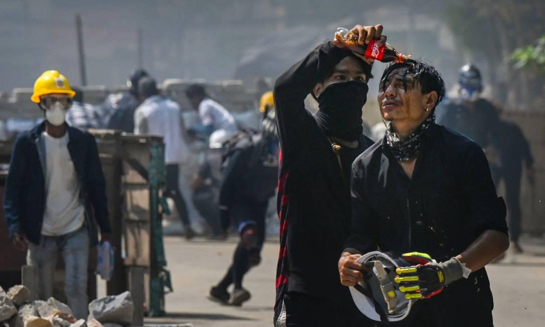 Manifestante derrama Coca-Cola no rosto de um companheiro para diminuir os efeitos do gás lacrimogêneo disparado pelas forças de segurança em uma manifestação contra o golpe militar no município de Thaketa, Mianmar Foto: STR / AFP
