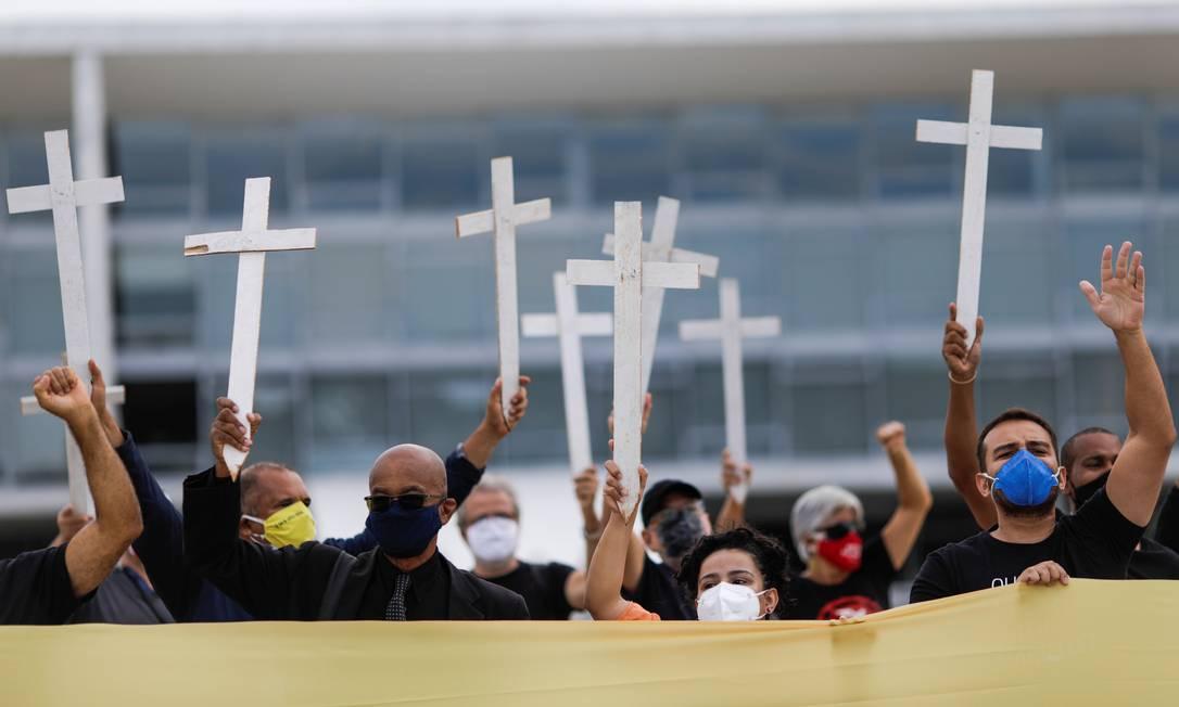 Os manifestantes também levaram cruzes para marcar os mortos pela pandemia de Covid-19. Foto: UESLEI MARCELINO / REUTERS