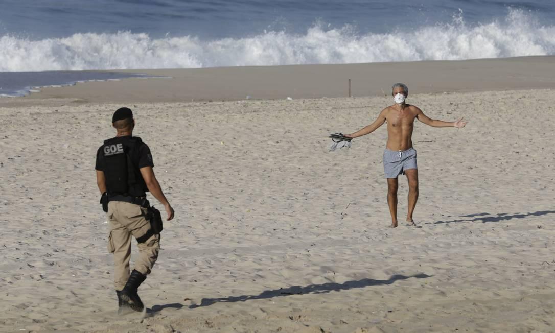 Banhista gesticula para agente ao ser retirado da praia de Ipanema Foto: Marcia Foletto / Agência O Globo